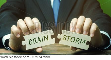 A Businessman Is Holding Wooden Puzzles With The Words Brainstorm. Creation Of New Ideas For Innovat