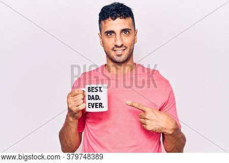 Young hispanic man drinking mug of coffe with best dad ever message smiling happy pointing with hand and finger
