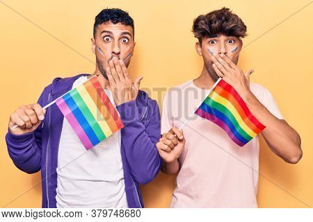 Young gay couple holding rainbow lgbtq flags covering mouth with hand, shocked and afraid for mistake. surprised expression