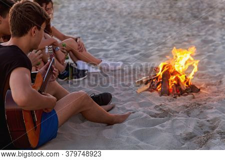 Group Of Friends Sitting With Guitar On The Beach Near The Campfire. Teenagers Have Fun On The Vacat