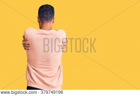 Young hispanic man wearing casual clothes hugging oneself happy and positive from backwards. self love and self care