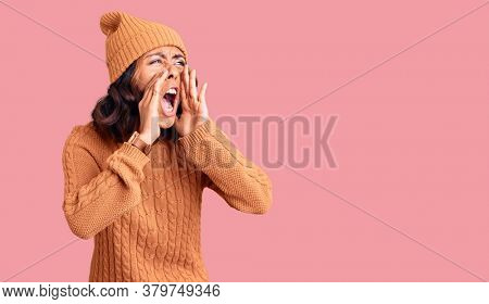 Young beautiful mixed race woman wearing wool sweater and winter hat shouting angry out loud with hands over mouth