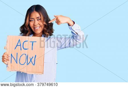 Young beautiful mixed race woman holding act now banner pointing finger to one self smiling happy and proud