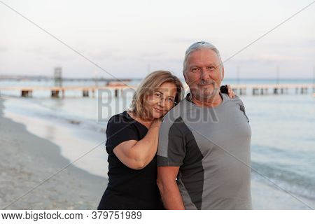 Portrait Of Happy Mature Man Being Embraced By His Wife At The Beach. Senior Couple Having Fun At Th
