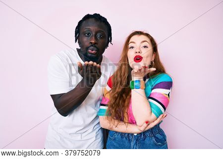 Interracial couple wearing casual clothes looking at the camera blowing a kiss with hand on air being lovely and sexy. love expression.