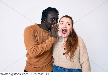 Interracial couple wearing casual clothes hand on mouth telling secret rumor, whispering malicious talk conversation