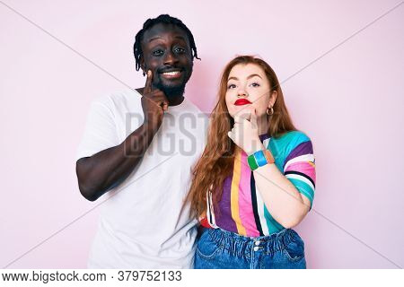 Interracial couple wearing casual clothes looking confident at the camera smiling with crossed arms and hand raised on chin. thinking positive.