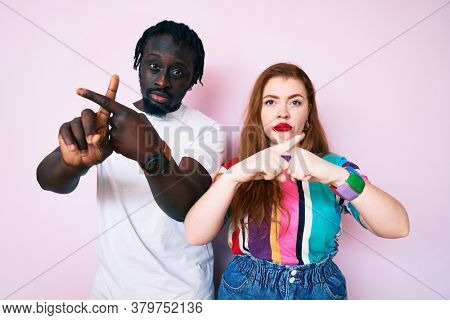 Interracial couple wearing casual clothes rejection expression crossing fingers doing negative sign