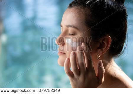Woman Applying Sunscreen Sunblock On Face Outdoors By Pool Under Sunshine. Summer Skin Care