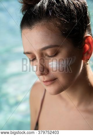 Young Beautiful Fit Woman With Sunscreen Sunblock On Her Cheeks Outdoors By Pool Under Sunshine. Sum