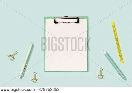 Flat Lay With Office Supplies, Paper Tablet With Clip, Blue And White Colored Pens, Ruler And Metal