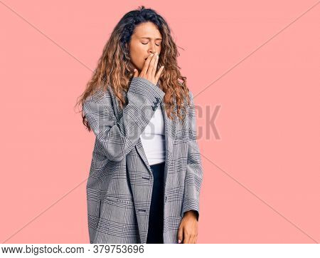 Young hispanic woman with tattoo wearing business oversize jacket bored yawning tired covering mouth with hand. restless and sleepiness.