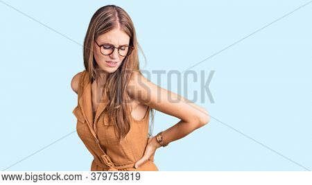 Young beautiful blonde woman wearing casual clothes and glasses suffering of backache, touching back with hand, muscular pain