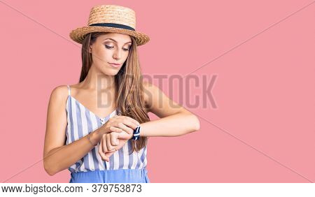 Young beautiful blonde woman wearing summer hat checking the time on wrist watch, relaxed and confident