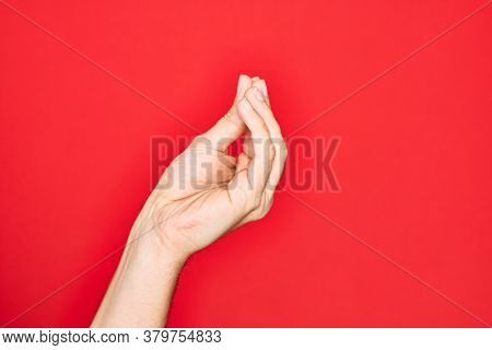 Hand of caucasian young man showing fingers over isolated red background doing Italian gesture with fingers together, communication gesture movement