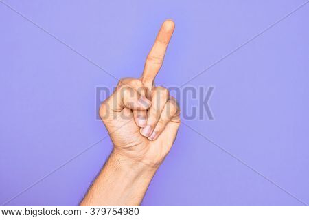 Hand of caucasian young man showing fingers over isolated purple background showing provocative and rude gesture doing fuck you symbol with middle finger