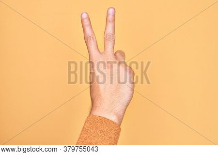 Hand of caucasian young man showing fingers over isolated yellow background counting number 2 showing two fingers, gesturing victory and winner symbol