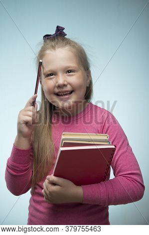 Little Girl With A Stack Of Books And A Pencil In Her Hands On A Blue Background. Back To School And