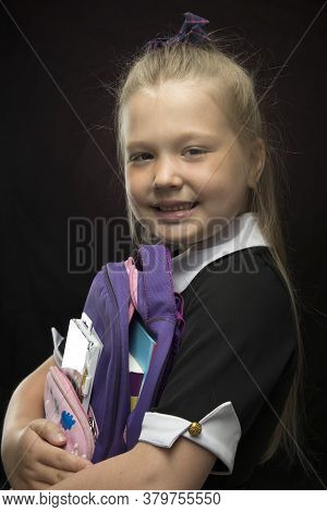 Little Girl With A School Backpack In Her Hands On A Black Background. Back To School And Education