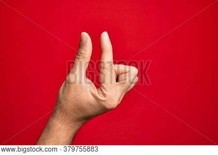 Hand of caucasian young man showing fingers over isolated red background picking and taking invisible thing, holding object with fingers showing space