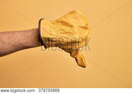 Hand of caucasian young man with gardener glove over isolated yellow background doing thumbs down rejection gesture, disapproval dislike and negative sign