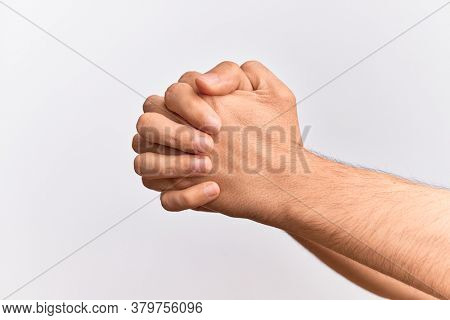 Hand of caucasian young man showing fingers over isolated white background praying with both hands clasped, fold fingers religious gesture