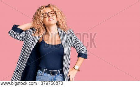 Young blonde woman with curly hair wearing business jacket and glasses suffering of neck ache injury, touching neck with hand, muscular pain