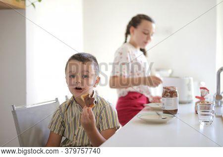 child eat chocolate in kitchen