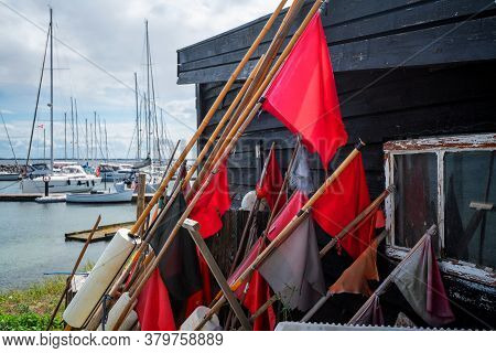Red Signal Flags At A Maritime Harbor With Sailing Boats In The Background