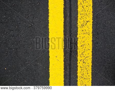 Close-up Yellow Dividing Lines On The Road With Copy Space. Yellow Double Solid Line. Road Markings