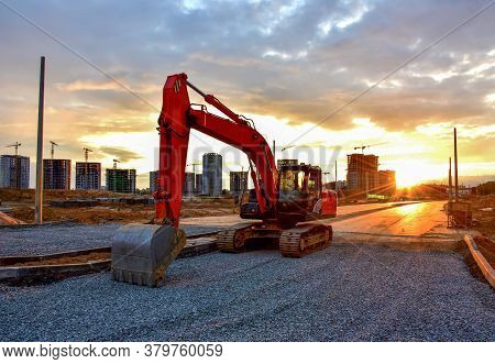 Excavator During Road Work At Construction Site On Awesome Sunset Background. Screeding Gravel For L