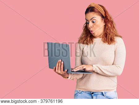 Young latin woman holding laptop scared and amazed with open mouth for surprise, disbelief face