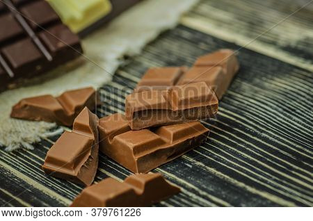 Milk Chocolate Bar. Chocolate Over Rustic Wooden Background.