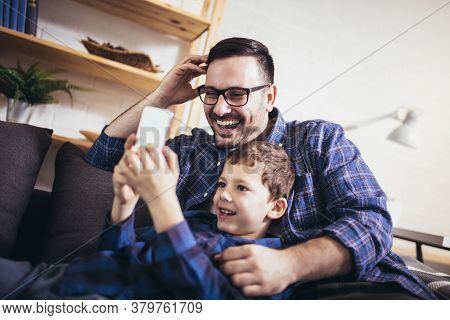 Young Father Embraces Little Son Family Sitting On Couch At Home Using Smart Phone Feels Happy Cheer