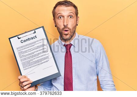Young handsome man holding clipboard with contract document scared and amazed with open mouth for surprise, disbelief face