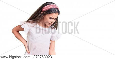 Cute hispanic child girl wearing casual white tshirt suffering of backache, touching back with hand, muscular pain