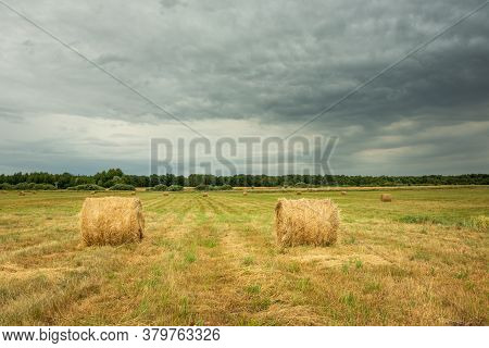 Hay Bales On The Hayfield And Dark Clouds On The Sky