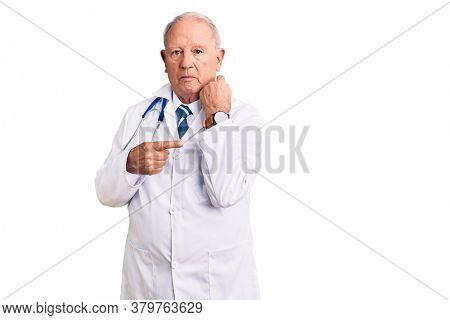 Senior handsome grey-haired man wearing doctor coat and stethoscope in hurry pointing to watch time, impatience, looking at the camera with relaxed expression