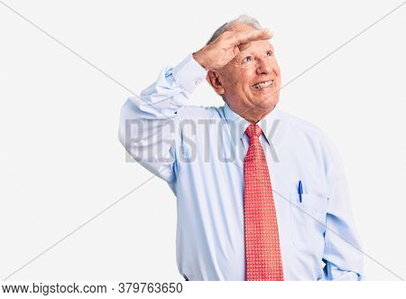 Senior handsome grey-haired man wearing elegant tie and shirt very happy and smiling looking far away with hand over head. searching concept.