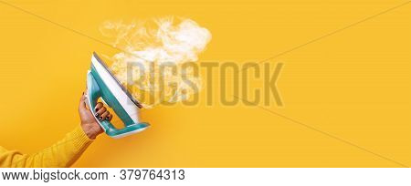 Modern Iron With Steam In Hand Over Yellow Background, Panoramic Mock-up Image