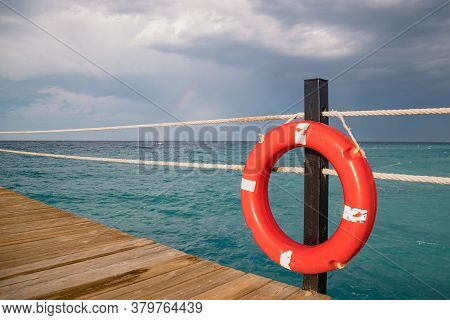 Red Lifebuoy On The Dock Against The Background Of The Stormy Sky Over The Sea