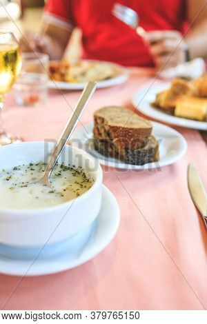 Turkish Vegetable White Cream Soup With In A Restaurant On The Table With A Glass Of Wine, Bread. Lu