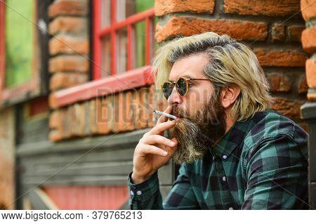 Brutal Caucasian Male In Glasses. Man Smoking Outdoor. Fashionable Mature Man Smoking Cigarette. Pun