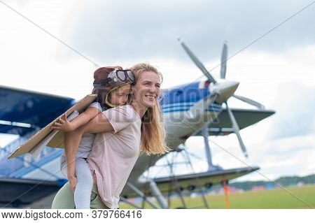 Beautiful Caucasian Woman Is Holding Her Little Daughter At The Airfield. A Small Girl In A Pilots C