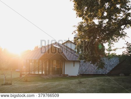 Old Wooden House In Village. Farmhouse In Belarus. View Of Rustic Ethnic House On Sunset. Rural Land