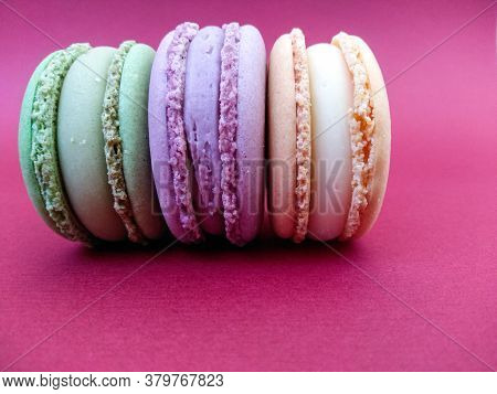 Beautiful Tasty Macaroon Cakes Lie On A Bright Pink Background. Orange, Violet, Green Macaroons On A