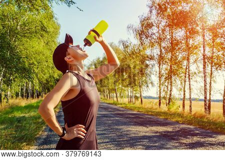 Resting Young Caucasian Woman Drinks Water From A Plastic Bottle After Hard Workout On The Countrysi