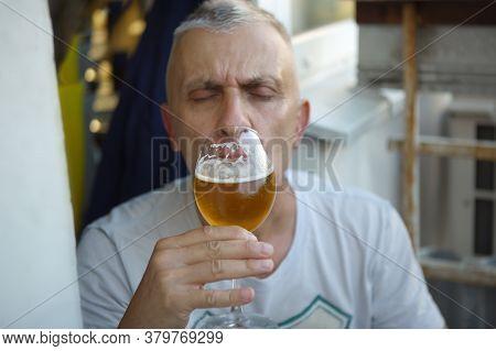 Portrait Of A Man Enjoying Beer With Shut Eyes, Outdoor Shot