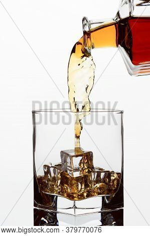 Whiskey Cognac Or Brandy Is Poured From A Transparent Bottle Into A Glass Cut Glass With Ice, Freezi
