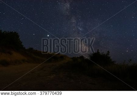 The Milky Way Over The Road. Beautiful Night Landscape With Starry Sky. The Planet Saturn And Jupite